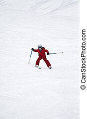 Young boy skiing down a snowy slope