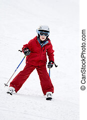 Boy skiing - Smiling young boy skiing down a snowy slope