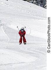 Boy skiing - Young boy skiing down a slope, ski poles tucked...