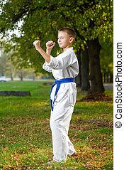 little boy in white kimono during training karate exercises...