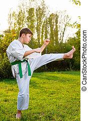 boy in white kimono during training karate exercises at...