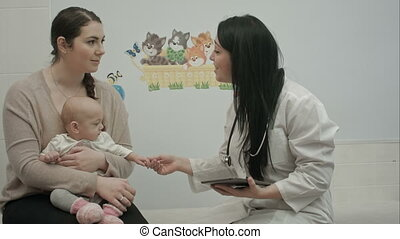 female pediatrician doctor shows something on tablet to...