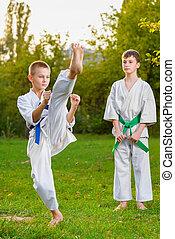 boys in white kimono during training karate exercises at...
