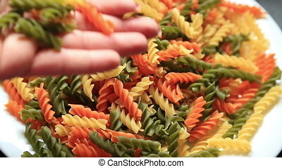 Colorful raw pasta pouring in a plate