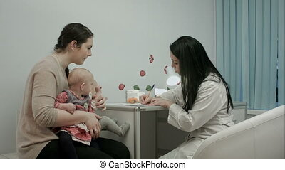 Pediatrician doctor at medical cabinet gives recommendations...