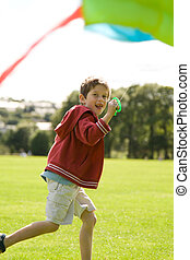 Boy flying a kite - Boy running and laughing with a kite
