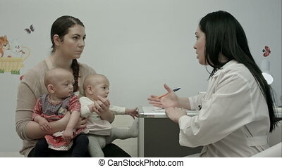 Female pediatrician doctor explain something to mother with...