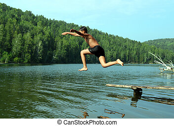 boy jumping in lake - summer vacations - boy jumping in lake