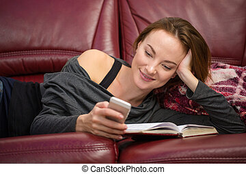 Smiling pretty woman reading book and using mobile phone -...
