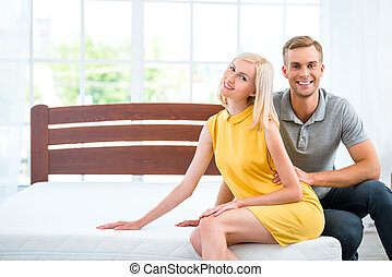 Young couple sitting on white bed