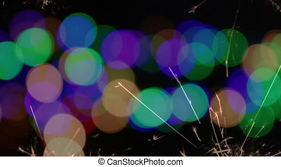 sparkler burning on blurry colorful backgrounds