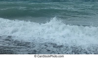 Sea waves and beach in cloudy day, in the summer