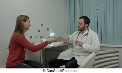 Beautiful medical representative presenting new product to doctor