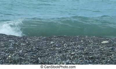 Pebbles beach and small waves, in the summer