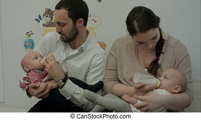 Young couple feed newborn twins from a bottle - Happy young...