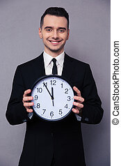 Smiling businessman holding wall clock - Portrait of a...