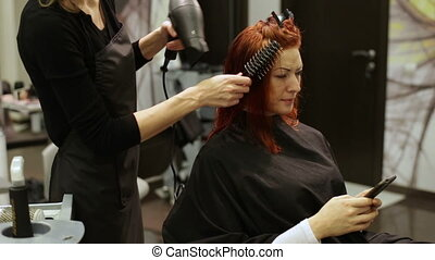 Hairdresser woman dries hair a hairdryer and comb - Pulling...