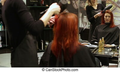 Woman looking in mirror as she makes hair styling - Pulling...