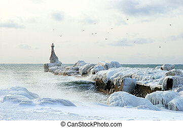 Icy pier - A marine pier and lighthouse freezing. Island...