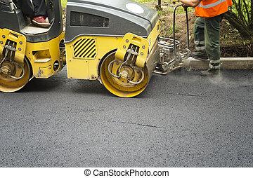 Road roller flattening new asphalt Compaction works
