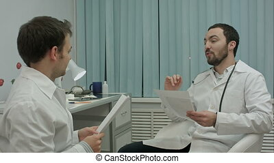 Bearded doctor shows new drugs to intern - Smiling bearded...