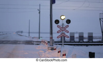 Railroad crossing, flashing warning sign. Evening time in winter.