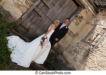 Happy wedding couple - Young wedding couple against a grunge...