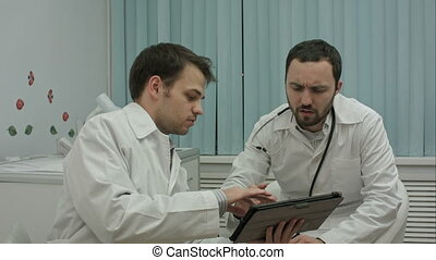 Male doctors watching on tablet pc and discussing results in...