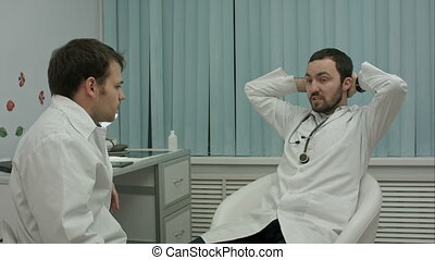 Two doctors relaxing at modern hospital indoors, speaking about life and work
