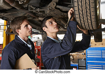 Mechanic And Trainee Working On Car Together