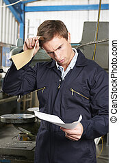 Factory Worker Reading Redundancy Letter