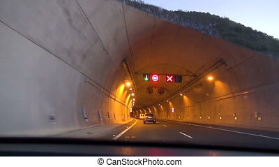 View of yellow lamp lit tunnel through the mountain shot...
