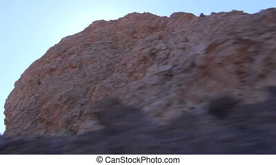 View of lava mountains through car - View of sunlit lava...