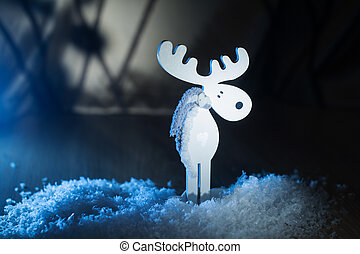 White wooden toy moose in the snow