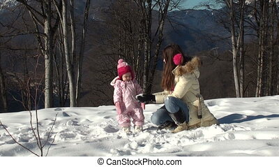 Happy mother playing snowballs with his daughter
