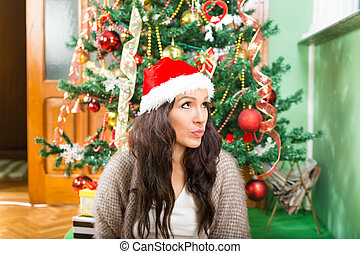Young woman wondering about Christmas presents and New Year...