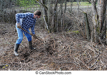 Manual Labor - A man using a stick to pick up a pile of...