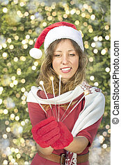 Beautiful Santa Claus girl with Christmas sparklers outdoors