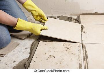 Installing ceramic tiles on a floor - Tiler installing...
