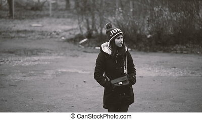 Lonely girl standing on the street in a jacket and hat Black...
