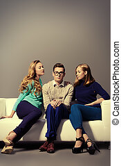 humble guy - A shy young man sitting on the couch with two...