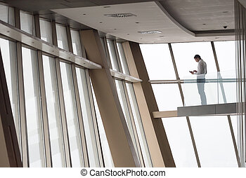 young successful business man in penthouse apartment working...