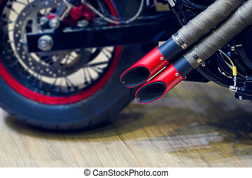 Red motorcycle exhaust pipe, modern style exhaust on wooden...