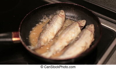 Fish is being fried on the frying pan.