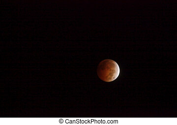 Lunar Eclipse - The glows red in the night sky during a full...