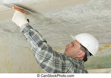 Pargeting - Contractor in white hardhat plastering the...