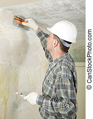 Pargeting - Contractor in white hardhat plastering the wall