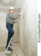 Plastering - Contractor on a ladder plastering a wall