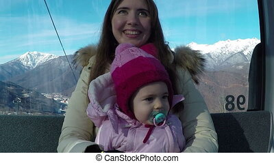 young mother with her little daughter riding on cableway in the mountains on a sunny day in winter