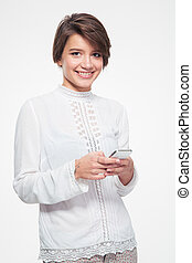 Smiling attractive young woman standing and using mobile...